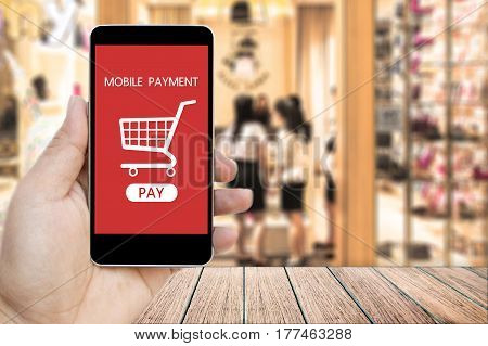 Hand holding smart phone with mobile payment and Shopping Cart on screen over blur people in the shopping mall background business and financial concept.