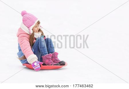 Joyful girl having fun and sledding on snow