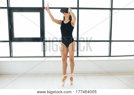 Beautiful young athletic woman (ballerina) with a beautiful figure standing near a window and looking into virtual reality goggles. Future technology concept. Modern imaging technology. Virtual reality glasses.