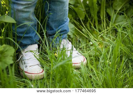 little kid boy in white sneakers and jeans standing on the green grass in the park. leg's shot. Child in white shoes. Walking in the park outdoors. top view.