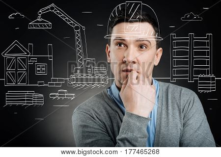 Plan your work. Thoughtful handsome professional construction engineer planning his work while standing on the construction set
