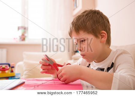 Cute kid boy crafting with scissors and color paper at his desk. Hobby activities for children. School child making some crafts.