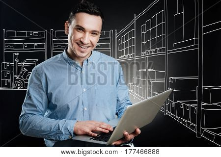 Plan all the work. Professional positive logist working in a depository and using laptop while sharing positivity