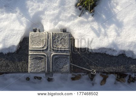 Holy water shell at a grave, wintertime
