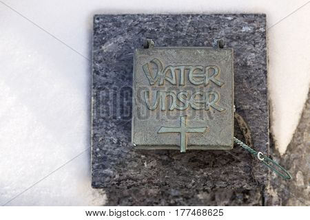 Holy water shell at a grave in wintertime