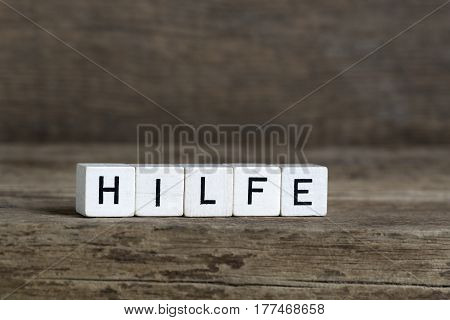 German word help written in cubes on a wooden background