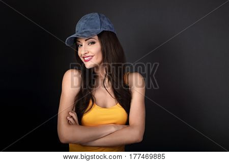 Beautiful Casual Smiling Woman In Blue Baseball Cap And Yellow Top Looking With Folded Arms On Grey