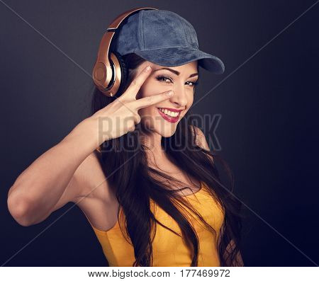 Joyful Teenager Listening The Music In Gold Wireless Headphone And Showing Victory V-sign Gesture In