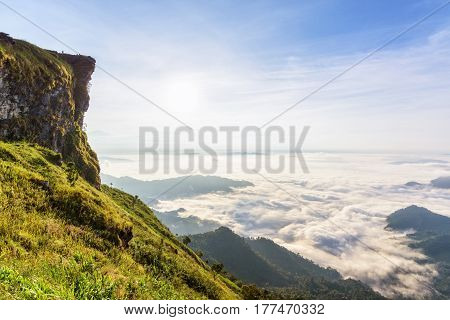 Beautiful landscape nature in morning on peak mountain with sun cloud fog and bright blue sky in winter at Phu Chi Fa Forest Park is a famous tourist attraction of Chiang Rai Province, Thailand