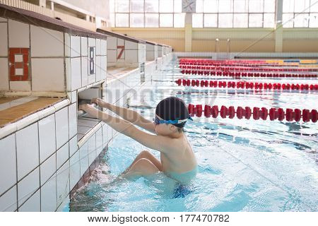 Cute little kid boy is ready for swimming competition in the sport swimming pool. Child ready to jump and swimming race. Training for competition. Sport activities for children indoors.