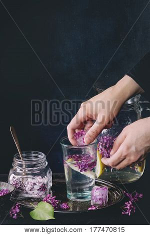 Female hands put ice cubes with flowers into glass of lilac lemonade with lemon. Glass jar of sugared lilac flowers and pitcher on black tablecloth over black. Dark rustic atmosphere. Toned image