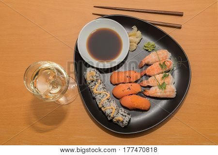 The sushi meal with a glass of white wine is ready