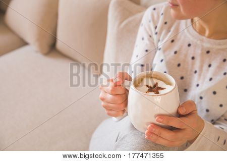 Girl with coffee mug sitting on the sofa indoors. Woman drinking a cup of coffee or tea sitting cozy at home. Relax and rest. Capuccino with cinnamon star.