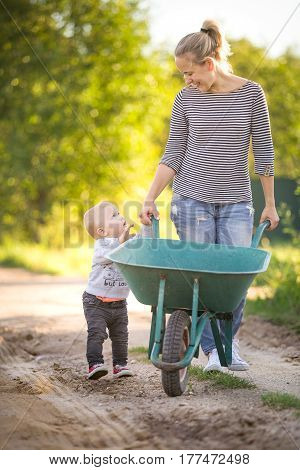 Adorable toddler boy and his mother walking along country road and pushing wheelbarrow on a sunny day. Summer works in the garden. Child helping mom.