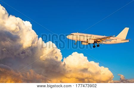 Airplane At Fly On The Sky With Clouds Sunset