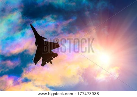 Silhouette of a fighter plane on a background of iridescent sky clouds and sun.