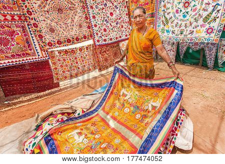 GOA, INDIA - MAR 1, 2017: Elderly woman trading an antique carpets and blankets for home during the market day in indian town on March 1, 2017. Near 5 million tourists visit Goa annually