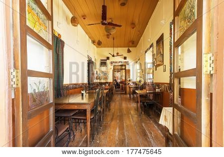 GOA, INDIA - MAR 1, 2017: People having rest inside empty room of vintage style cafe in indian city on March 1, 2017. Near 5 million tourists visit Goa annually