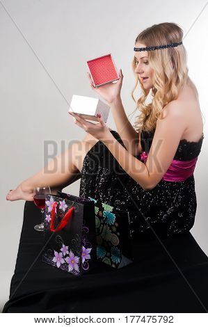 Young attractive woman opens box with gift and is surprised over white studio background