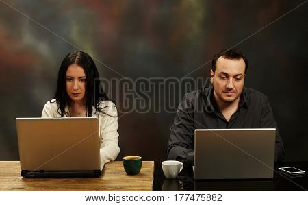 Woman and man working on a laptops.