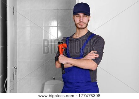 Young plumber holding pipe wrench in bathroom