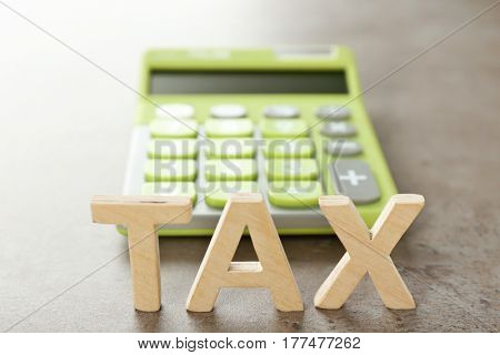 Word TAX and calculator on grey background