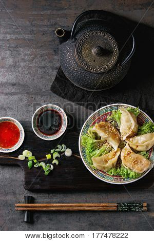 Gyozas potstickers on lettuce salad with sauces. Served in traditional china plate with chopsticks and black teapot on wood serving board over old metal background. Top view, space. Asian dinner