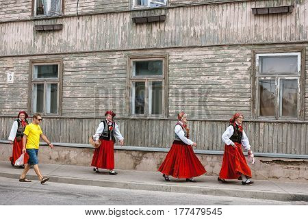 SABILE LATVIA - JULY 28 2012: Four women in traditional latvian folk costumes walk down the street of Sabile and looks at the young guy in jeans shorts and yellow t-shirt
