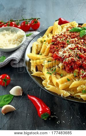 Hot Penne pasta bolognese with parmesan cheese, basil, Garlic, tomatoes, chili on plate