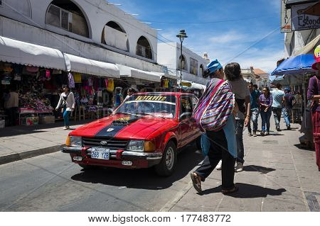 Sucre Bolivia - December 1 2013: People and a car in a street in the city of Sucre in Bolivia.