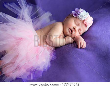 Newborn girl sweetly asleep with a wreath on her head