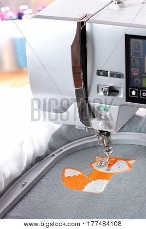 Embroidery with embroidery machine - fox theme - upright, view on machine, fabric and blurry background