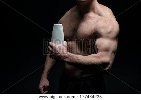 Handsome Bodybuilder Man With Muscular Body Holds Shampoo Bottle