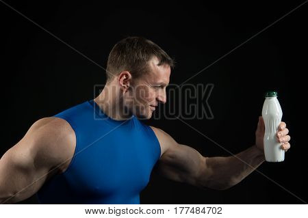 Handsome Bodybuilder Man With Muscular Body Holds Drink Bottle