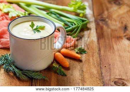 Vegetable soup puree with cheese in a white mug and vegetables on wooden background