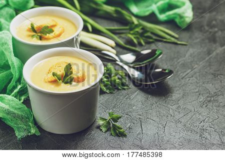 Two bowls of vegetable soup puree with croutons and vegetables in the background