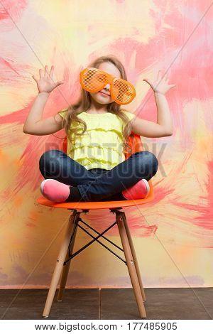 Small Happy Baby Girl In Orange Sunglasses And Yellow Shirt