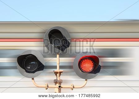Rail road crossing flashing against the background of a moving train