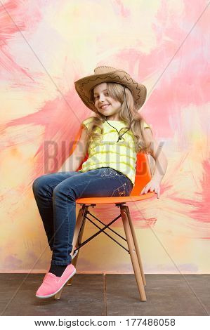 Small Happy Baby Girl In Cowboy Hat On Orange Chair