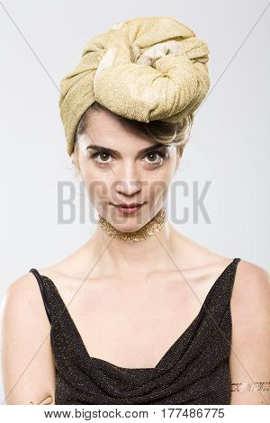 Portrait of expressive woman with golden turban on white background