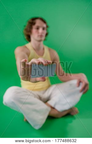 Young man doing yoga and holding card. Shallow depth of field.