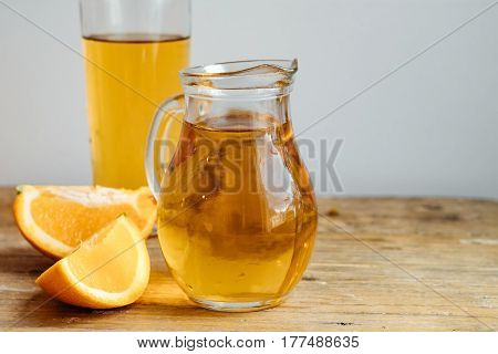 Homemade Kombucha In A Decanter With Orange  On A Wooden Table. Copy Space