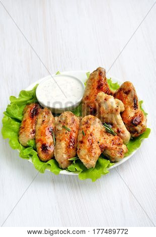 Appetizer roasted chicken wings on lettuce leaves on white wooden plate