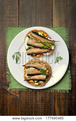 Appetizing sandwiches with sprats and egg on white plate top view
