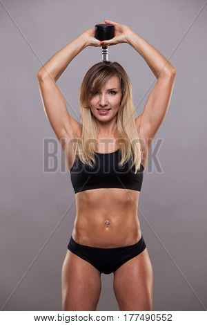 Beautiful athletic woman pumping muscles with a dumbbell on the back, isolated on grey background with copyspace.