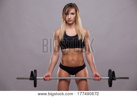 Beautiful athletic woman in sporty cloths is pumping muscles with a barbell, isolated on grey background with copyspace.