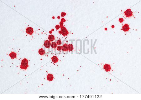 Red blood drops on white snow-liked felt background. Criminal or violence concept