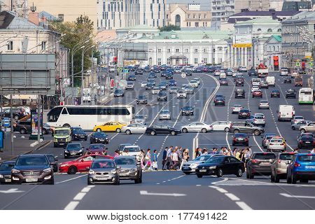 MOSCOW - AUGUST 19 2016: Group of pedestrians cross Sadovaya-Spasskaya street while cars turn left. This avenue is a part of The Garden Ring road