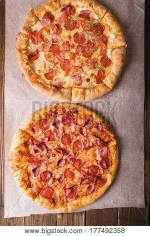 Rustic pizza with salami mozzarellabasil top view with copy space. Two pizzas on a wooden table. Pizza salami on wooden background