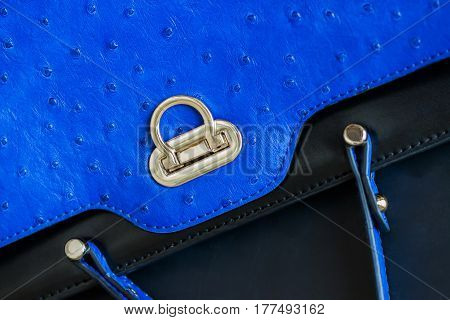 Close-up texture of vivid fashion blue color handbag from genuine leather with embossed under the skin of Ostrich, gold lock. Concept of shopping, manufacturing, lifestyle